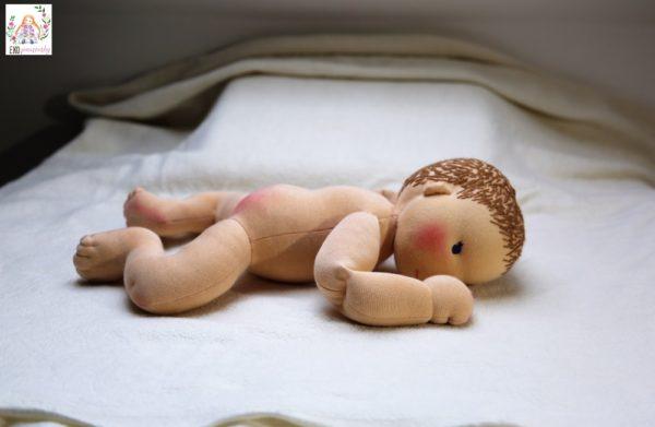 velké miminko leží na bříšku, látková panenka