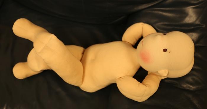Veliká demonstrační panenka pro rehabilitaci si hoví na gauči, Ekopanenky