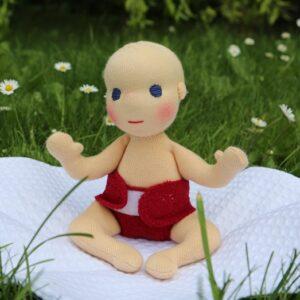 ručně šitá panenka, waldrorfské malé miminko sedící v trávě