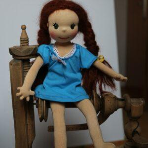Panenka v modrých úpletových šatičkách sedí na kolovrátku