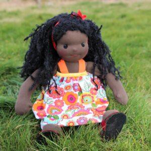 sedící látková panenka černoška v trávě