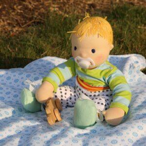 Ručně šitá panenka batole si hraje v sedě na dece
