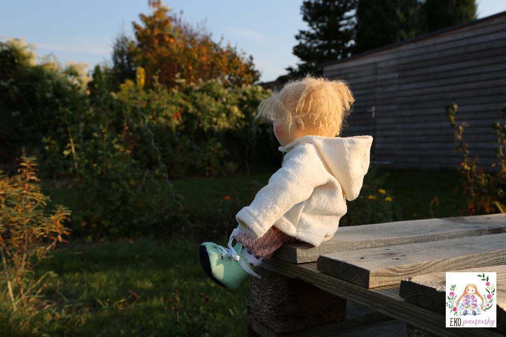 Sladká holčička, waldorfská panenka batole sedící v kabátku na zahradě, ekopanenky